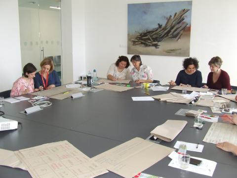 Egy nagy, széles asztal körül ülnek a képzésen résztvevők, párokba rendeződve, és kicsoportos munkába elmélyedve. Az asztal nagy részét a munkához szükséges papírok, füzetek borítják.