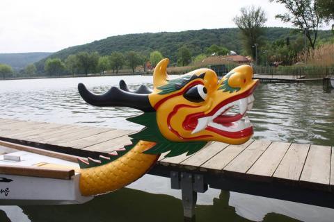 A képen egy sárkányhajó orrán elhelyezett, faragott, kínai stílusú sárkányfej látható, tátott szájjal, kilátszó fogazattal. A háttérben dombok között hullámzó tó, valamint egy deszkázott stég, melyhez a hajó ki van kötve.